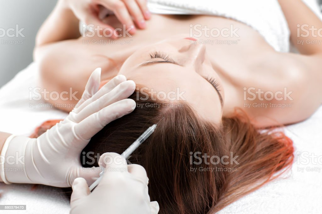 Needle mesotherapy. Cosmetic been injected in woman's head. stock photo