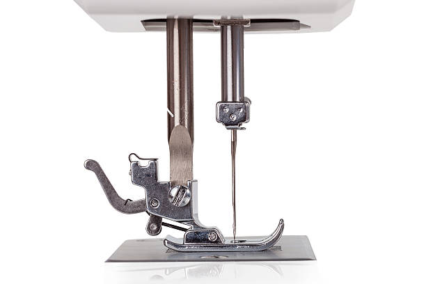 needle, plate, foot and transporter of an electric sewing machine - sewing machine needle stock photos and pictures