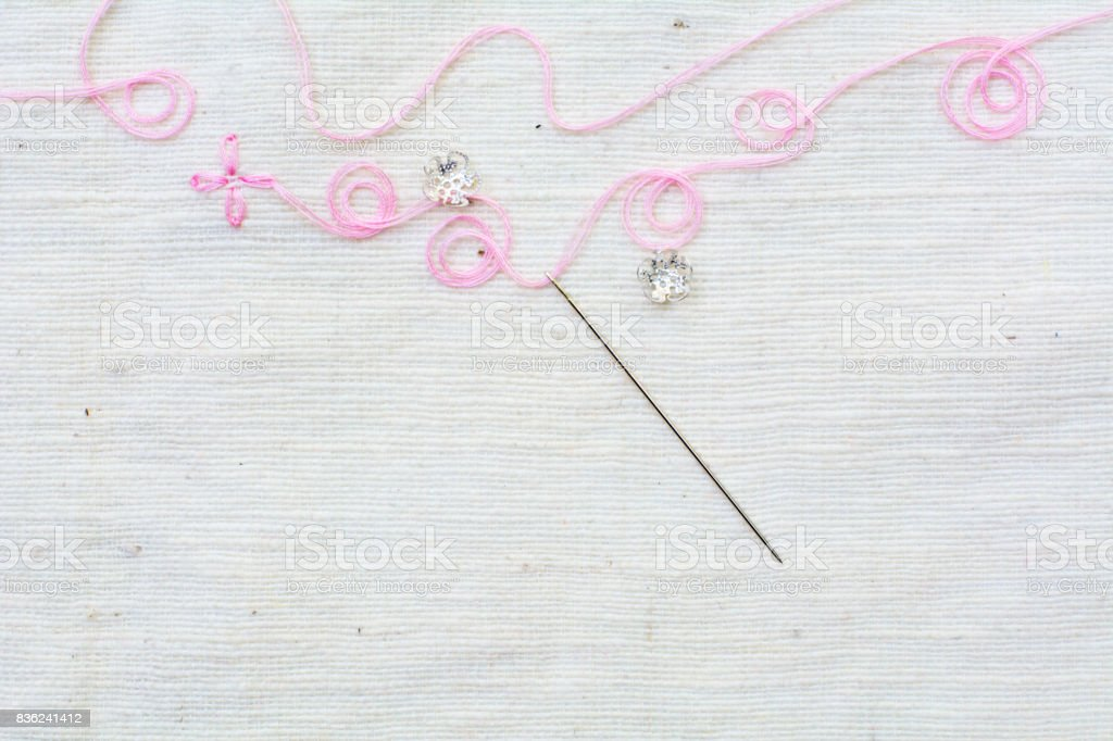needle with pink thread on white cotton background stock photo