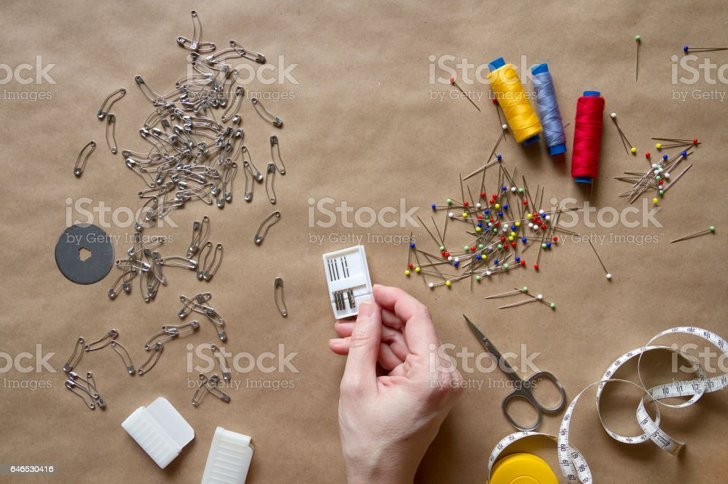 Needles in human hand and sewing supplies стоковое фото