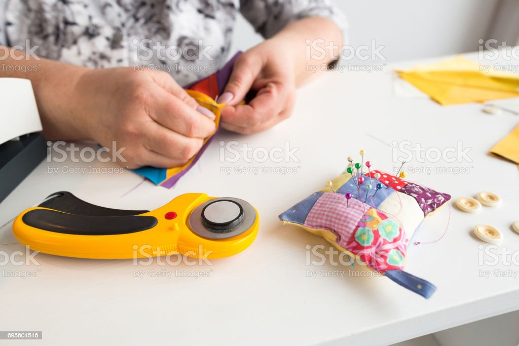 needlework and hand quilting - tailor hands sew multicolored patchwork fabric with the use of needles, cushions for pins, buttons and rotary fabric cutters on white background stock photo