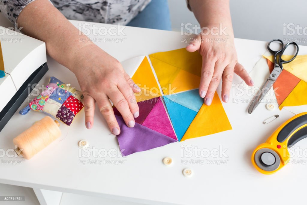 needlework and quilting in the workshop of a tailor woman on white background - tailor at work with pieces of colored cloth on the table with threads, fabrics, needles, sewing machine, rotary cutters stock photo