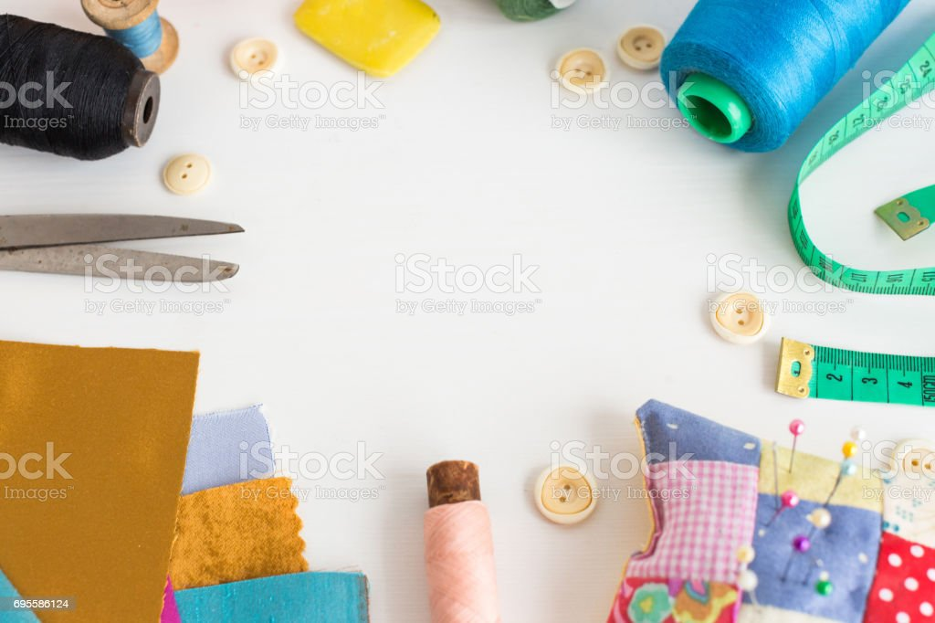 needlework, craft, sewing and tailoring concept - tools close-up on white desk, measuring meter, pink, blue and black thread spools, scraps of colorful fabric, pin and pincushion, white buttons, soap stock photo