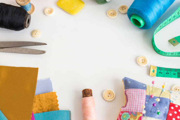 needlework, craft, sewing and tailoring concept - tools close-up on white desk, measuring meter, pink, blue and black thread spools, scraps of colorful fabric, pin and pincushion, white buttons, soap - seam stock photos and pictures