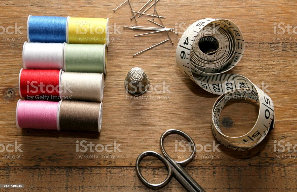 Needlework essentials on a wooden sewing table stock photo