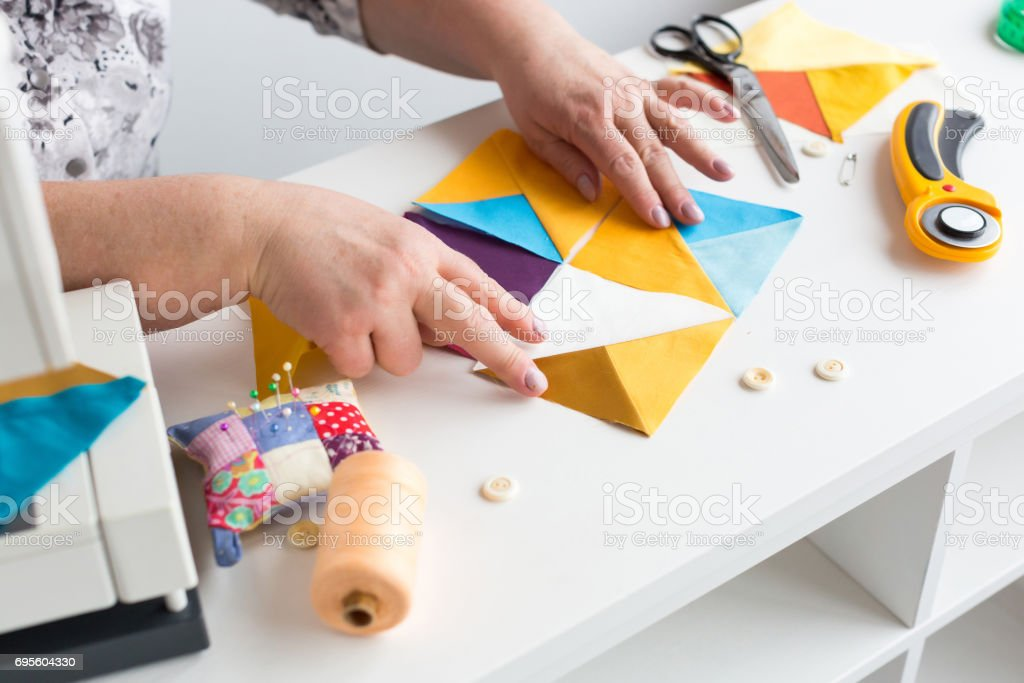 needlework hand quilting in the workshop of a tailor woman on white background - the hands of tailor collect from the desktop scraps of colored fabric for patchwork on the sewing machine stock photo