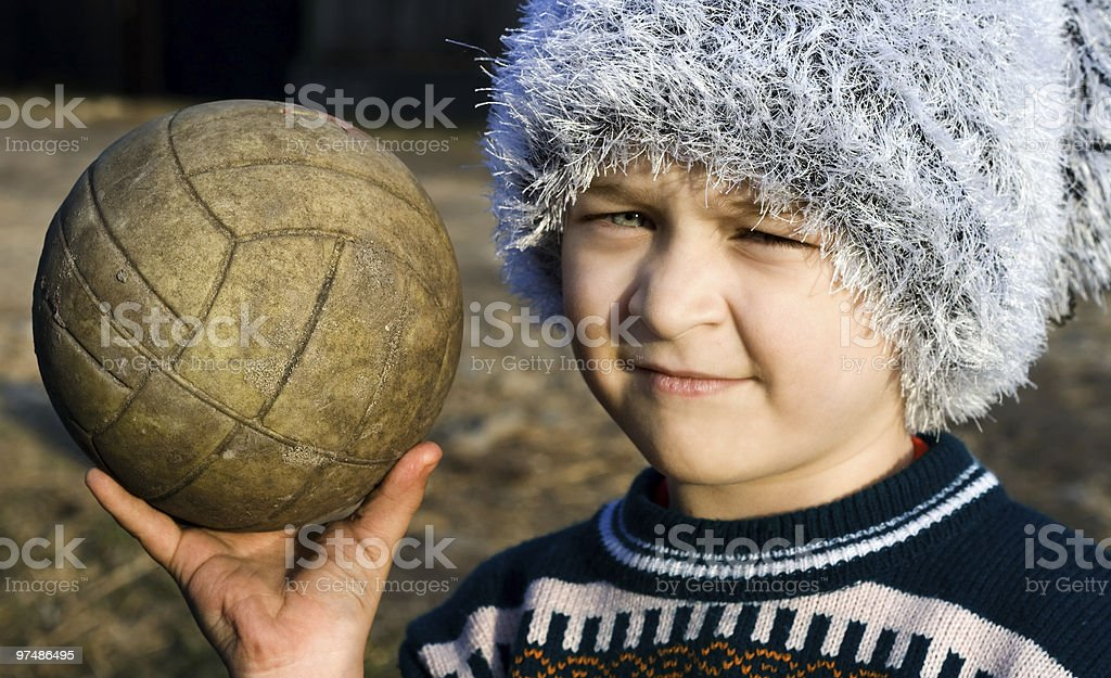 Needy boy with warn ball in his hand royalty-free stock photo