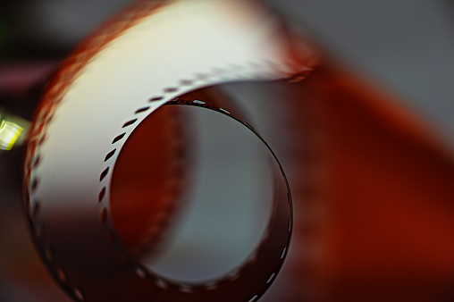 Negative photographic coil on a dark background, close-up.