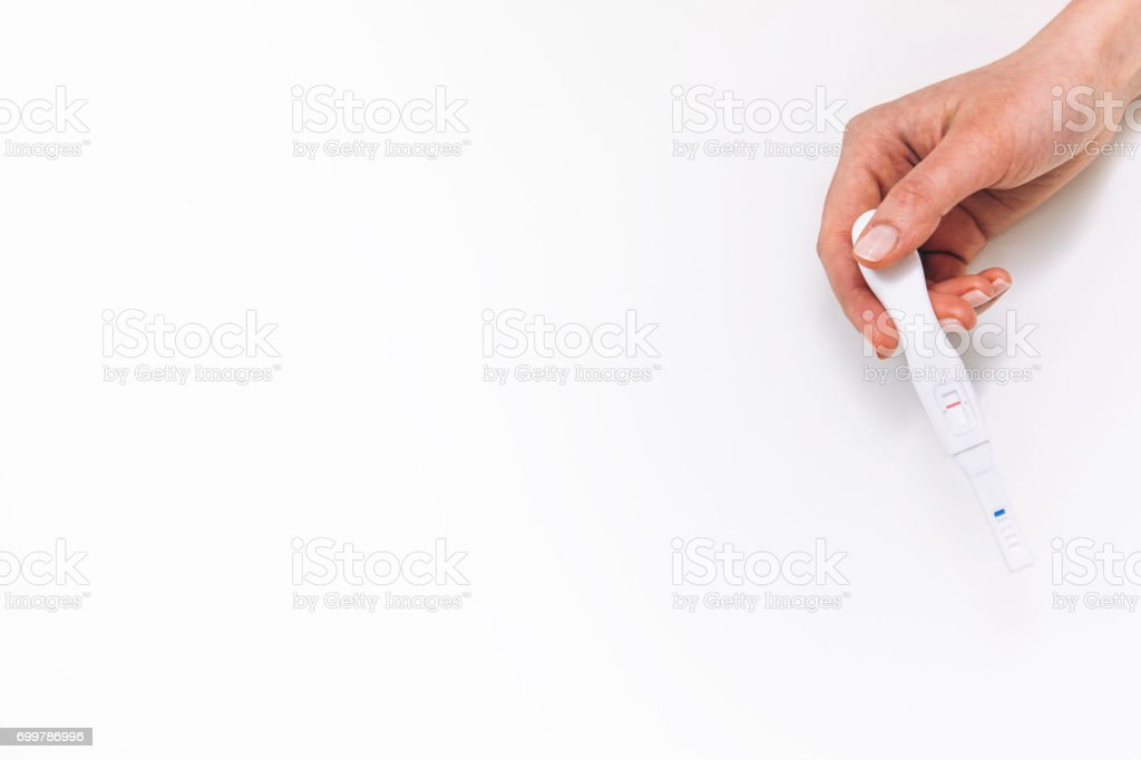 Negative pregnancy test in female hand, flat lay stock photo