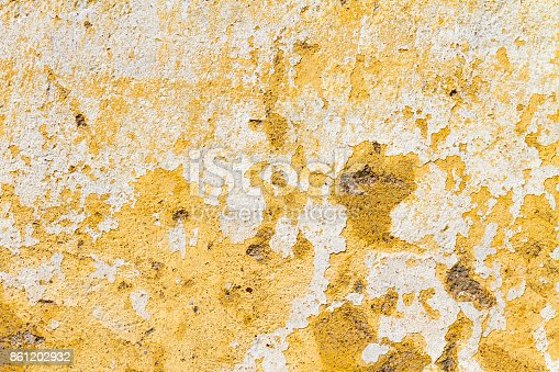 Old and neglected peeled wall with layers of white and yellow paint; Architectural background, texture, pattern; Copy space, sign board.