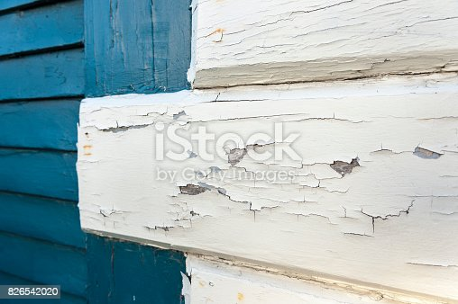 White paint flaking from boards on old building
