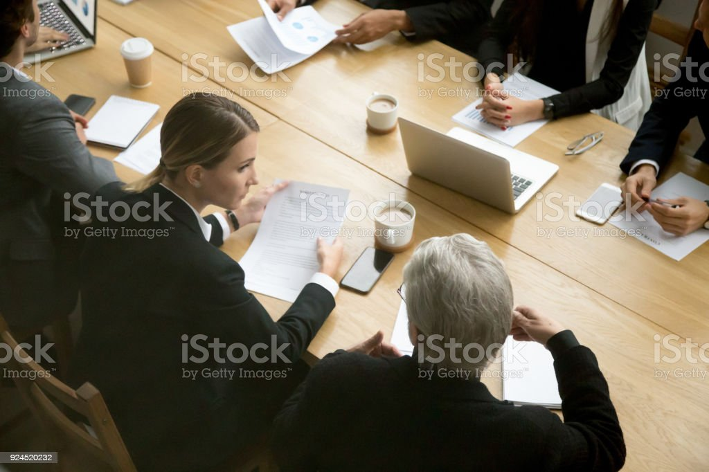 Negotiations concept, different businesspeople discussing deal details at group meeting stock photo