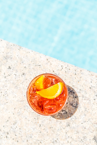 istock Negroni cocktail  near a pool at the resort bar or suite patio. Luxury resort, vacation, room service concept 1078150960