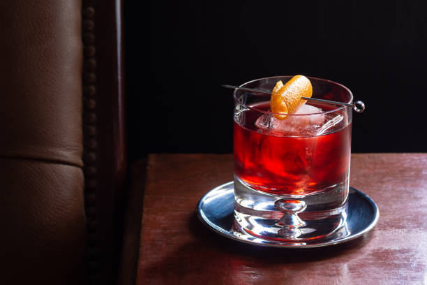 Negroni Cocktail, with Gin, Red Vermouth, and Campari, over Ice with Orange Twist in Dark Luxurious Bar stock photo