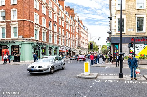 1125782554 istock photo Neighborhood district of Kensington street brick architecture and road traffic with shopping stores and people crossing Stanhope Gardens 1125993260
