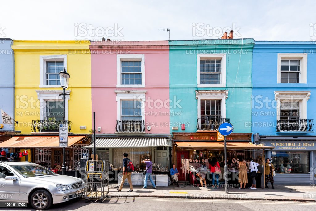 Neighborhood district of Notting Hill, street, colorful multicolored famous style flats architecture facade, road, people shopping in iconic center, Portobello stock photo