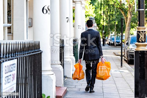 London, UK - June 22, 2018: Neighborhood district of Pimlico, Gloucester Street, businessman man carrying grocery shopping bags after work in evening walking home by architecture traditional style flats