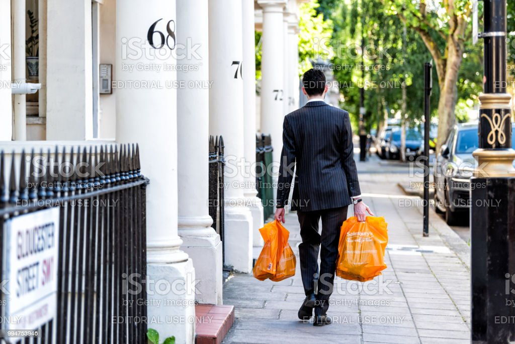 Neighborhood district of Pimlico, Gloucester Street, businessman man carrying grocery shopping bags after work in evening walking home by architecture traditional style flats stock photo