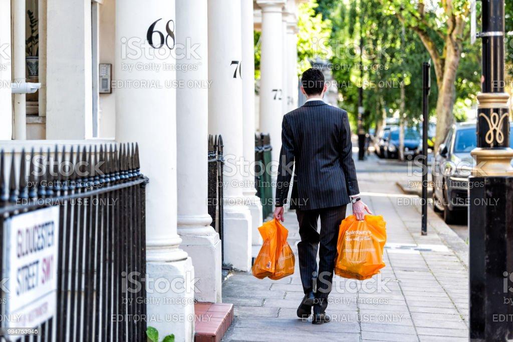 Homem de negócios de Gloucester Street, distrito de Pimlico, bairro carregando sacolas de compras de supermercado, depois do trabalho na noite a pé para casa por apartamentos de estilo tradicional de arquitetura - foto de acervo