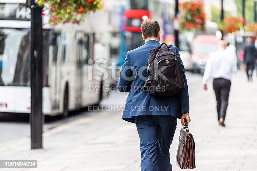 istock Neighborhood district of Pimlico Street, businessman man walking with briefcase and backpack before or after work 1081604094