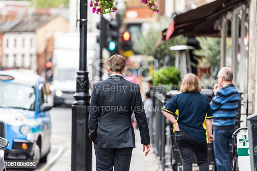 istock Neighborhood district of Pimlico Street, businessman man walking with ear phones listening to music before or after work 1081605680