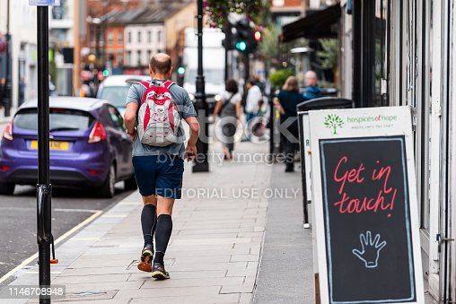 512860403 istock photo Neighborhood district of Pimlico Street with man walking or running by sign placard 1146708948