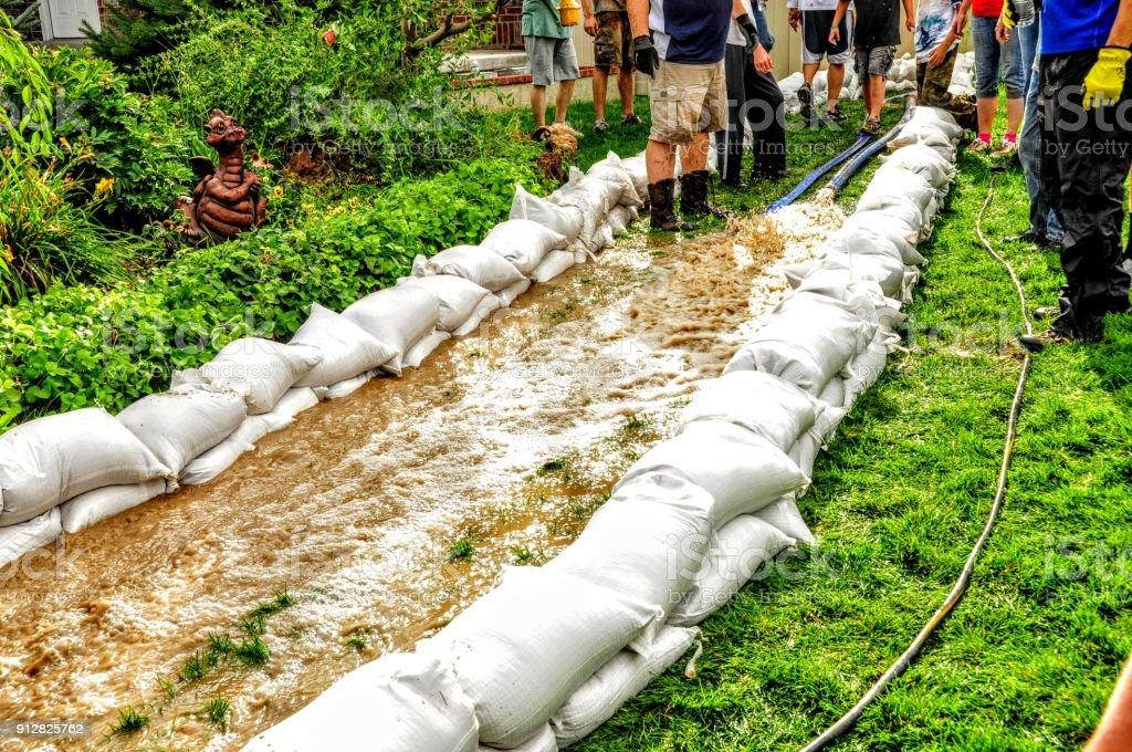 Neighborhood Flood, Volunteers devote themselves to prepare the sandbags to channel the water. stock photo