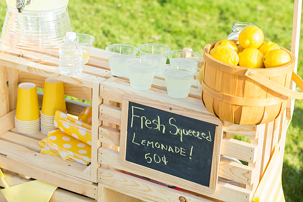 Neighborhood lemonade stand A lemonade stand is set up in the front yard of a home in the suburbs. A basket full of fresh lemons and glasses of lemonade are sitting on the stand. A chalkboard lists the price of the lemonade. lemonade stand stock pictures, royalty-free photos & images