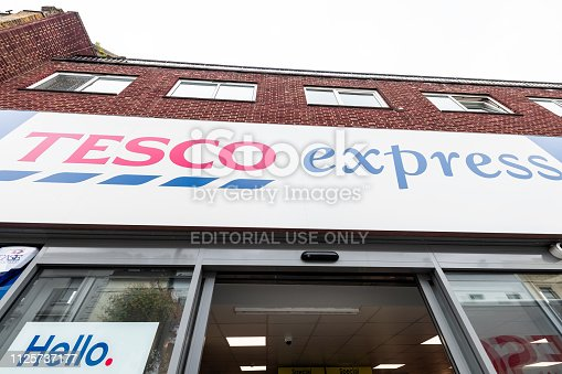 512860403 istock photo Neighborhood local store Tesco Express blue grocery shopping storefront facade exterior entrance with sign closeup in Pimlico 1125737177