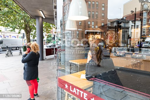 istock Neighborhood of Pimlico Victoria with woman standing on sidewalk by Pret A Manger cafe restaurant window reflection 1125735080