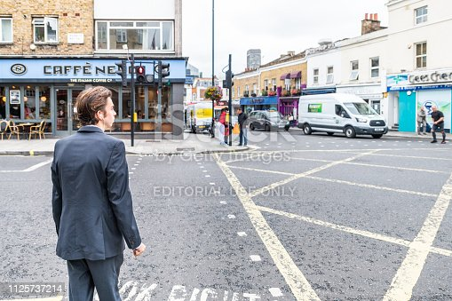 istock Neighborhood of Pimlico with road and cafe Nero restaurant and one business man people waiting to cross street 1125737214