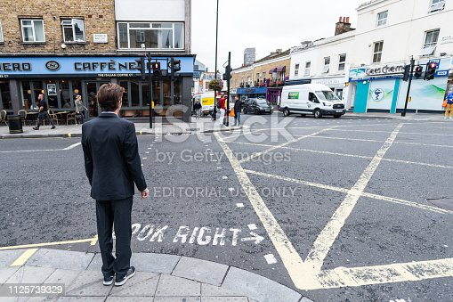istock Neighborhood of Pimlico with road and cafe Nero restaurant and one young business man people waiting to cross street 1125739329