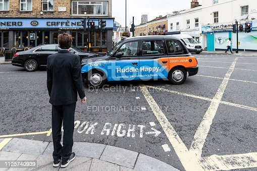 istock Neighborhood of Pimlico with road and cafe Nero restaurant and one business man waiting to cross street with taxi cab car 1125740939