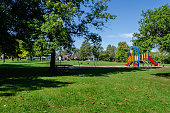 Neighborhood park and playground area on a summer day with shade and a blue sky,