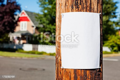 Photo of a blank sheet of white paper fastened to a wooden electrical pole, neighborhood houses visible in the background.