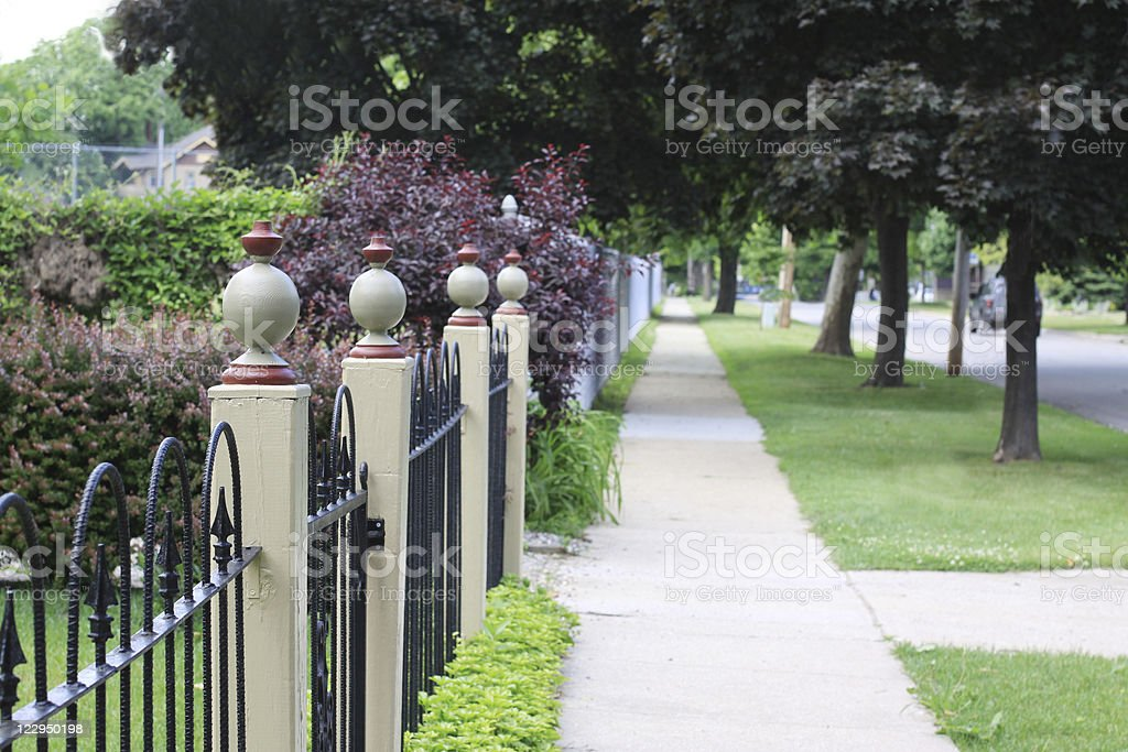 Neighborhood Sidewalk with Fence Posts stock photo