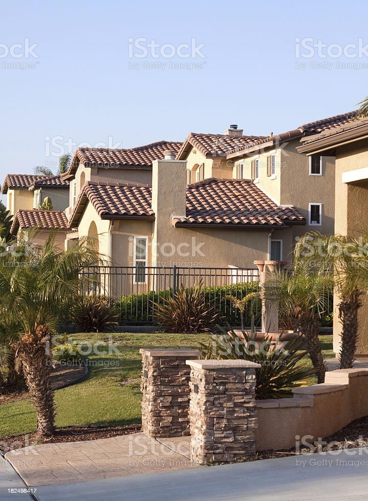 Neighborhood Stucco Home Exterior and Blue Sky stock photo