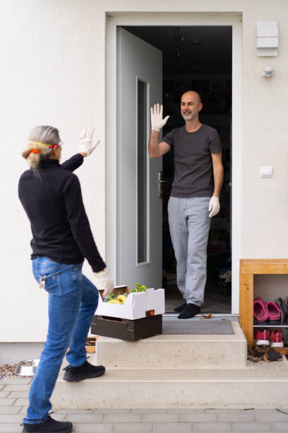 neighborly help during coronavirus crisis with social distancing, woman delivering boxes with food stock photo