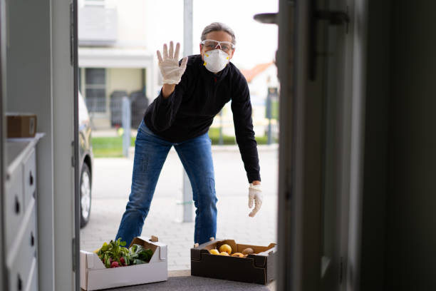 neighborly help during covid-19, friendly waving woman delivering fresh food stock photo