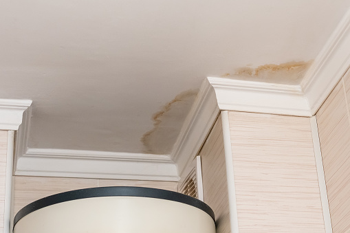 Neighbors have a water leak, water-damaged ceiling, close-up of a stain on the ceiling.