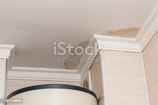 istock Neighbors have a water leak, water-damaged ceiling, close-up of a stain on the ceiling 1287049885