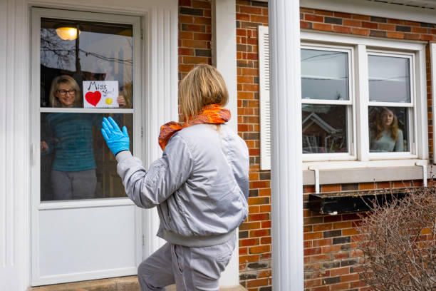 Neighbors helping each other.  A friend drops by for a chat on the doorstep. Two women chatting on the front doorstep of a residential home.  The woman outside delivering a gift is wearing protective gloves and a face mask.  They are practicing social distancing. flatten the curve stock pictures, royalty-free photos & images