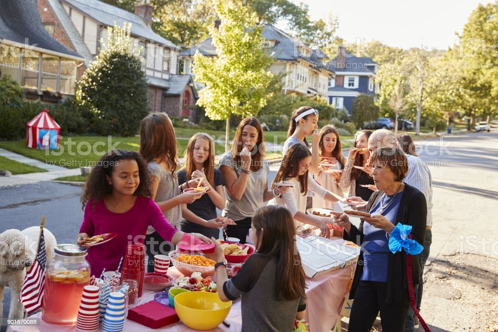 Neighbours helping themselves to food at a block party stock photo