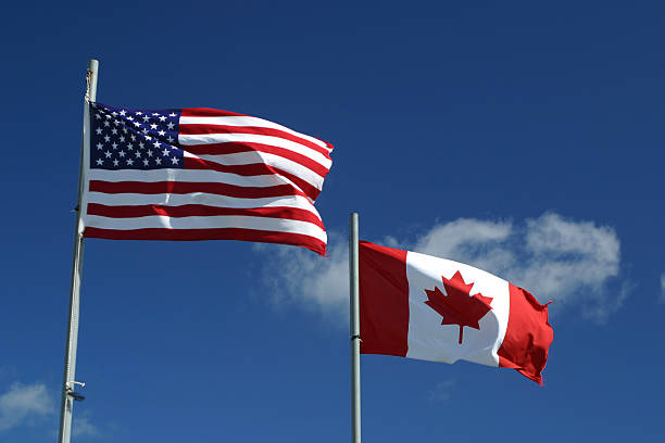 Neighbours of North America US and Canadian flags wave in wind on graduated blue background with clouds. We have numerous American and Canadian flag images in our portfolio. geographical border stock pictures, royalty-free photos & images
