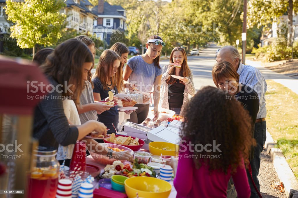 Neighbours standing around a table at a block party stock photo