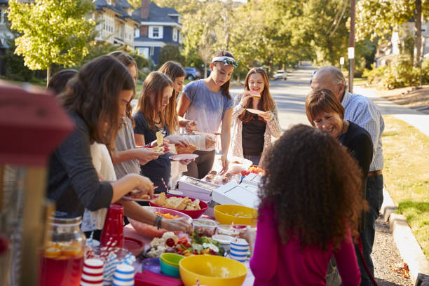 neighbours standing around a table at a block party - vicino foto e immagini stock