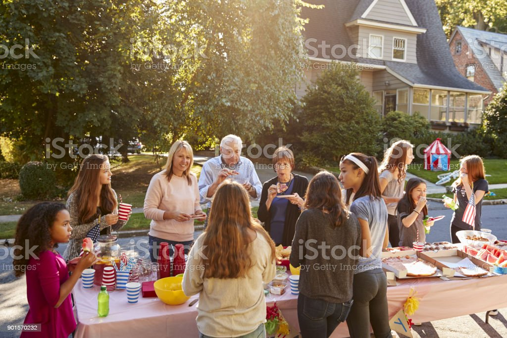 Neighbours talk and eat around a table at a block party stock photo