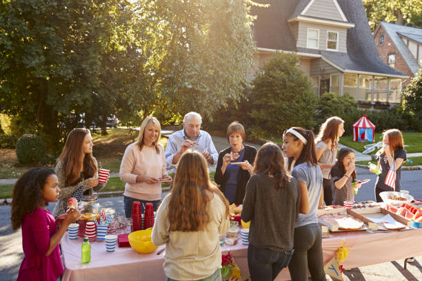 neighbours talk and eat around a table at a block party - vicino foto e immagini stock