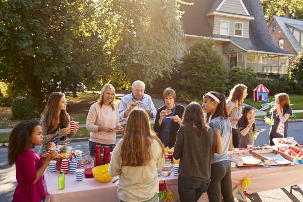 neighbours talk and eat around a table at a block party - vizinho imagens e fotografias de stock