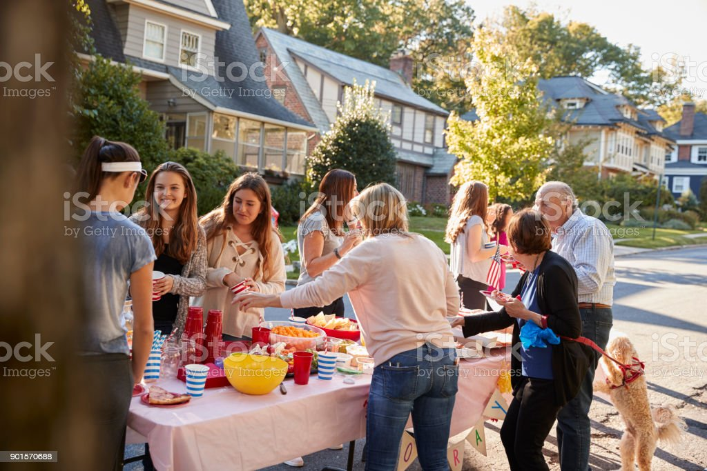 Neighbours talk standing around a table at a block party stock photo